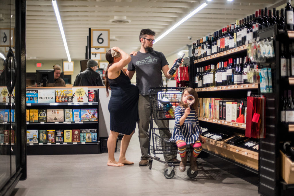 Woman in labor at the co-op, while man looks at wine.